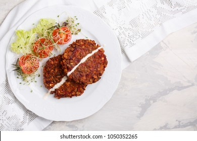 Vegan burgers from lentils, oats and vegetables. Veggie cutlets served with green salad and tomatoes. Healthy food concept. Top view. Copy space.