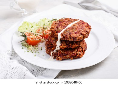Vegan burgers from lentils, oats and vegetables. Veggie cutlets served with green salad and tomatoes. Healthy food concept.