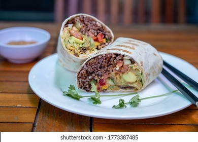 Vegan burrito. Sliced up raw food wrap with vegan ingredients on a plate. Close up
