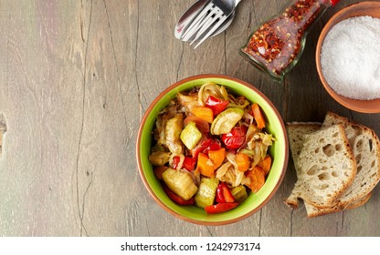 Vegan cabbage, carrot, paprika and zucchini stew. Portion of sauteed vegetables with artisan bread on vintage wooden table. Close up top view with copy space