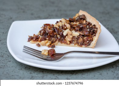 Vegan cake with dates and walnuts, baked homemade on white plate. Close up