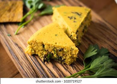 Vegan carrot, pumpkin cheese pieces on wooden board. Cooked with agar seaweed, coconut oil, parsley, dill and garlic. Raw, vegan, vegetarian healthy food concept.
