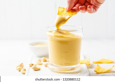 Vegan cashew cheese sauce in a glass, white background. Plant based food concept.