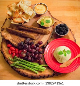 Vegan charcuterie snack platter on a two tiered wooden serving tray