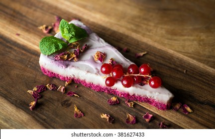 Vegan cheesecake with rose petals and red currant