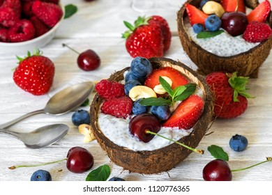 Vegan chia seeds pudding with fresh berries, nuts and mint in coconut bowls with spoons over white wooden table. healthy breakfast. close up