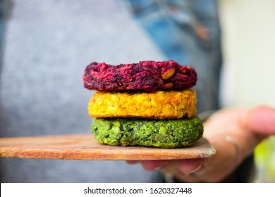 Vegan chickpea burgers cutlets or patties. Healthy vegan diet food. Woman hands holds mixed vegetables yellow pumpkin, orange carrot, green spinach and red beet bean cutlets with wooden spatula