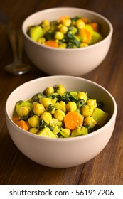Vegan chickpea curry or chana masala with spinach, potato and carrot, photographed with natural light (Selective Focus, Focus one third into the first curry)