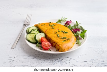 Vegan chickpea omelet with bell peppers served with tomatoes, cucumbers, lettuce and parsley on a light gray textured background. Healthy homemade food
