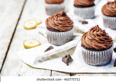 Vegan chocolate banana cupcakes with chocolate cashew cream frosting. toning. selective focus
