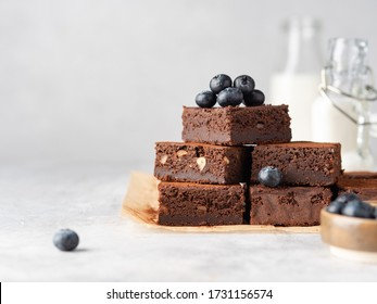 Vegan chocolate brownie with nuts and blueberry. Brownie chewy squares stack with fresh berries and cocoa powder on baking paper. Morning table. Copy space. White background.