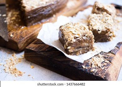 Vegan chocolate cake stuffed with oats and coconut flakes on parchment paper and wooden board. Sweet healthy diet dessert. Vegetarian food.