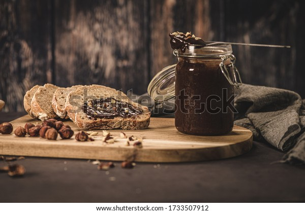 Vegan chocolate spread made of organic almond butter and organic cacao and honey, on dark rustic kitchen counter top.