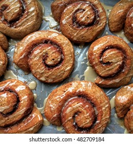 Vegan cinnamon buns baked with 100% whole wheat flour, fresh out of the oven, and drizzled with sweet glaze on a baking tray.