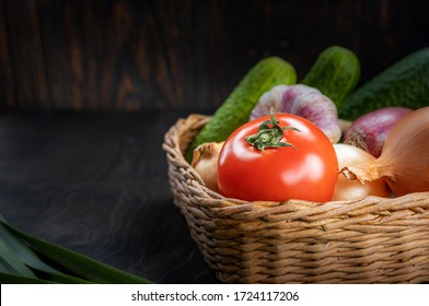 Vegan concept, healthy food, organic vegetables in a basket on a dark background, in a rustic style, the main object is a tomato in focus, illuminated moonlight, shallow depth of field