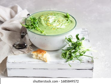 Vegan cream soup with avocado and spinach served with micro greens and bread. Diet food concept. Vegetarian and vegan food.