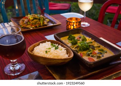 vegan cuisine with drinks on a table set for two. These healthy options are Thai Green Curry with white rice and Pad Thai. Glasses of white wine and beer are also on the candlelit table
