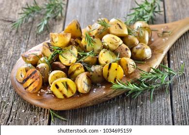 Veganische Küche: Grillkartoffeln mit Rosmarin auf Holzbrett