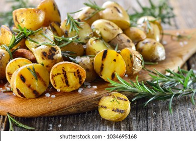 Vegan cuisine: Grilled baby potatoes with rosemary served on a wooden board