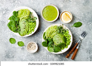 Vegan, detox Buddha bowl with avocado, spinach, micro greens, edamame beans, zucchini noodles and herb green dressing. Top view, grey concrete background