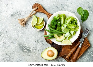Vegan, detox Buddha bowl with avocado, zucchini noodles, green beans, spiralized cucumber, tomatoes, broccoli, lime. Top view, grey concrete background