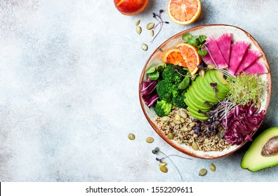 Vegan, detox Buddha bowl with quinoa, micro greens, avocado, blood orange, broccoli, watermelon radish, alfalfa seed sprouts. Top view, flat lay, copy space