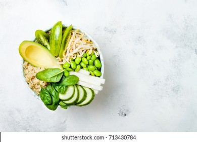 Vegan, detox green Buddha bowl recipe with quinoa, avocado, cucumber, spinach, tomatoes, mung bean sprouts, edamame beans, daikon radish. Top view, flat lay, copy space
