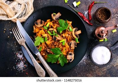Vegan dish. Fried mushrooms and cabbage in the frying pan. European cuisine.