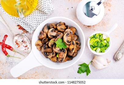Vegan dish. Fried mushrooms and onion in the frying pan. European cuisine.