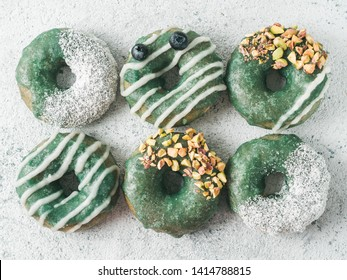 Vegan doughnuts with chia seeds topped with healthy spirulina glaze with pistachio, desiccated coconut and blueberry. Blue green spirulina donuts, on gray background, top view or flat lay