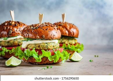 Vegan falafel burger with vegetables and sauce, dark background. Healthy food concept.