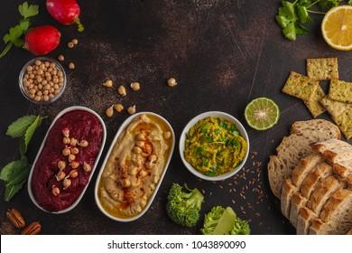 Vegan food background. Vegetarian snacks: hummus, beetroot hummus, green peas dip. Top view, dark background, copy space.