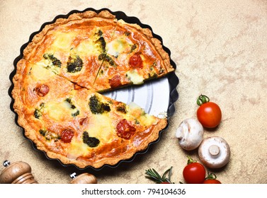 Vegan food in cafe or restaurant. Pizza pie in metal baking dish near food decor. Traditional rustic cuisine concept. Vegetarian pizza with tomatoes, broccoli and cheese on beige background.