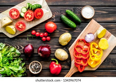 Vegan food cooking with raw vegetables on dark wooden background top view