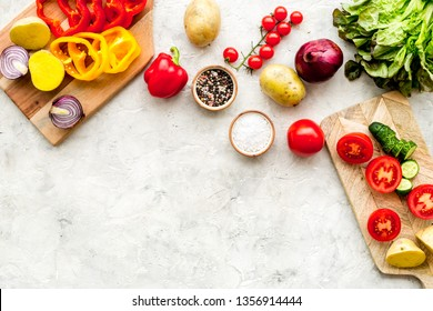 Vegan food cooking with raw vegetables on white stone background top view mock up