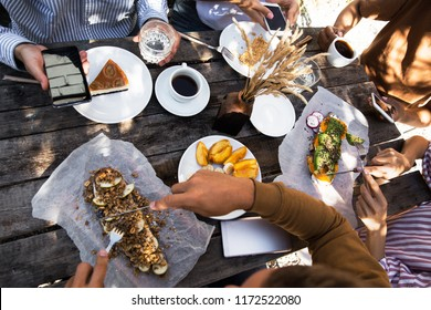 Vegan food, holidays, leisure and people concept, top view of happy friends having picnic outdoors relaxing lying on plaid blanket and eating
