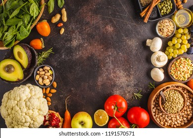 Vegan food ingredients on a dark background. Vegetables, fruits, cereals, nuts, beans top view. Plant based diet concept.