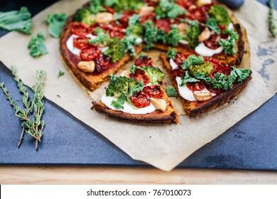 Vegan Gluten Free Pumpkin Crust Pizza with Kale, Sun dried Tomatoes and Mozzarella. Selective Focus, Toning.