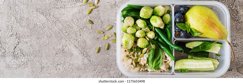Vegan green meal prep containers with  rice, green beans,  brussel sprouts, cucumber and fruits. Dinner in lunch box. Banner. Top view. Flat lay