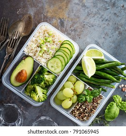 Vegan green meal prep containers with quinoa, rice, avocado and vegetables overhead shot with copy space