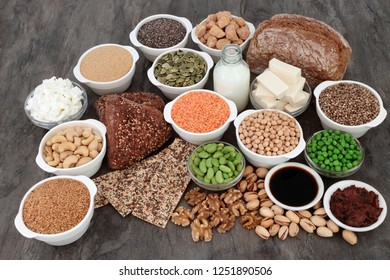 Vegan health food with tofu bean curd, legumes, nuts, seeds, wholegrain bread, miso, soy sauce, vegetables, grains, almond yoghurt and milk. High in antioxidants, omega 3, protein & dietary fibre.
