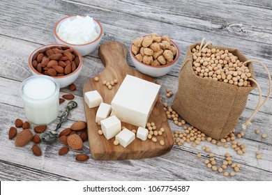 Vegan health food with tofu, soy beans, nuts, yoghurt, soya milk and chunks. Foods high in fibre, antioxidants, vitamins and minerals. On rustic wood background.