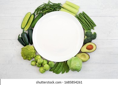 Vegan health food wreath with green vegetables to boost the immune system surrounding a white empty plate on rustic wood. Foods high in vitamins, minerals, antioxidants & dietary fibre. Ethical eating
