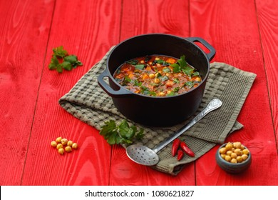 Vegan Indian cuisine, Sweet Potato and Chickpea Masala in black iron pot with green napkin on red old wooden background, top view, overhead