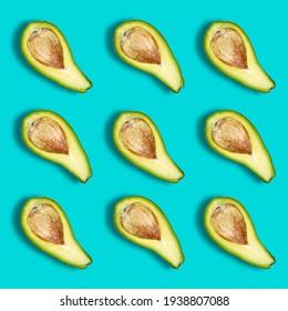 Vegan or lean menu, salad ingredients. Pattern of ripe avocado halves on green. An avocado with a bone in a diagonal arrangement.