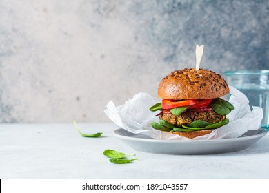Vegan lentil burger with baked sweet potato, tomato sauce and fresh vegetables on a gray plate. Vegan food concept.