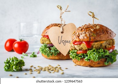 Vegan lentil burgers with kale and tomato sauce on a white background. Plant based food concept.