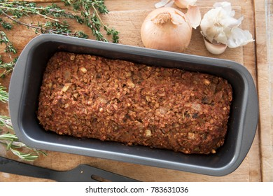 Vegan lentil loaf in baking pan on cutting board with some ingredients, view from above