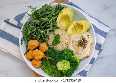Vegan lunch bowl with quinoa, hummus, chickpeas, avocado, vegetables