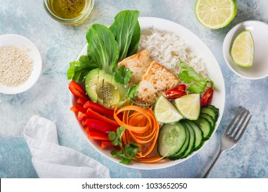 vegan lunch bowl salad with roasted tofu cheese, avocado, rice, cucumber, bell pepper, carrot and pak choi, top view, copy space